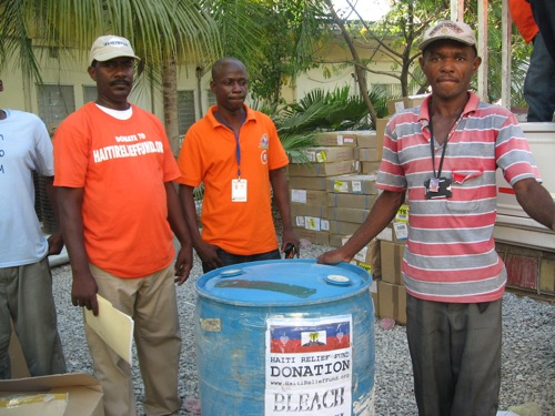 November 25, 2010: Mr. Allain Demessier from Haiti Relief Fund, Inspector Yves Saul from the Bureau of the Ministre of L'Interieur Direction Protection Civile, Mr. Hector Paultre from CTC Cholera Treatment Center receiving 1 barrel of bleach for CTC Centre GHESKIO to help fight cholera in Haiti.