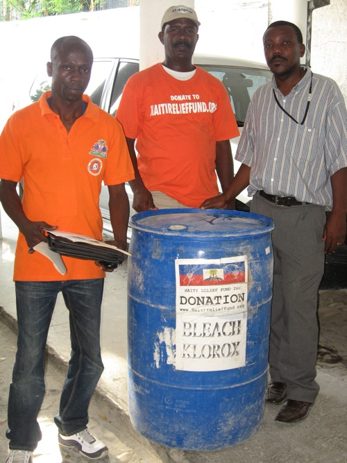 November 25, 2010: Haiti Relief Fund donation of 1 barrel of bleach to fight cholera at CTC, Cholera Treatment Center, Hospital De L'Ofatma Port-au-Prince, Haiti. Inspector Yves Saul from the Bureau of the Ministre De L'Interieur Direction Protection Civile, Mr. Allain Demerisier from Haiti Relief Fund and Mr. Origen Jean Claude from CTC Centre L'OFATMA receiving the donation.