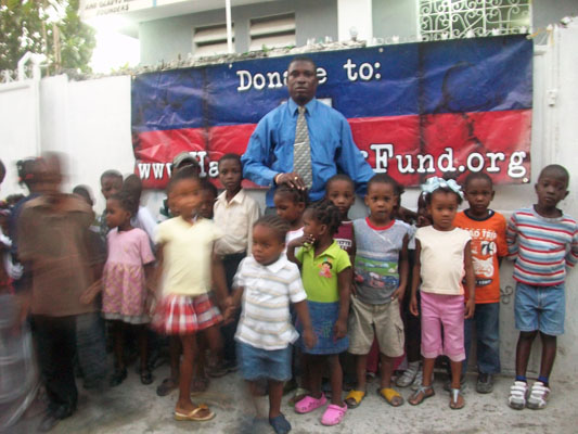 Pastor Dominique with children in Waney, Carrefour, Haiti Relief Fund donated clothing, shoes, and stuffed animals toys for Christmas 2010.